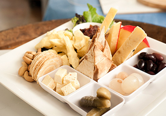 Platter of cheeses, pickled onions, gherkins, olives, nuts and biscuits.